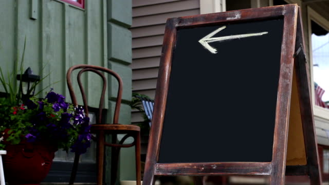 woman walks by foldout sign with arrow pointing to business in small town - marciapiede video stock e b–roll