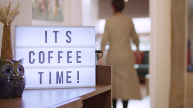 Woman walks in and Switches on Decorative Lightbox Written It's Coffee Time! in Comfy and Cozy Home
