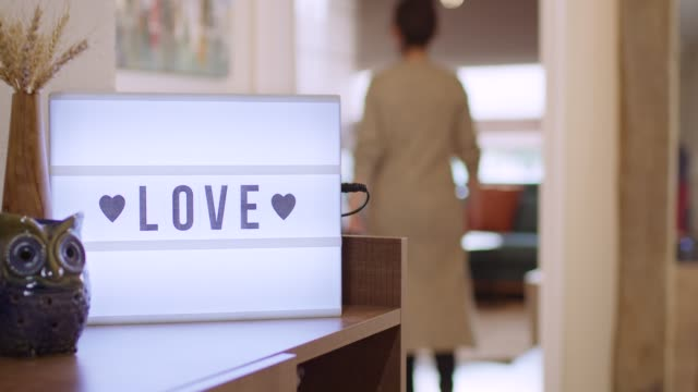 "Woman walks in and Switches on Decorative Lightbox Written Love in Comfy and Cozy Home Home indoor scene with ""Love"" written on white light box and woman entering from right side then switches on light box and walks out the scene. home icon stock videos & royalty-free footage"