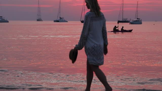 Woman walks into calm sea surf at sunrise video