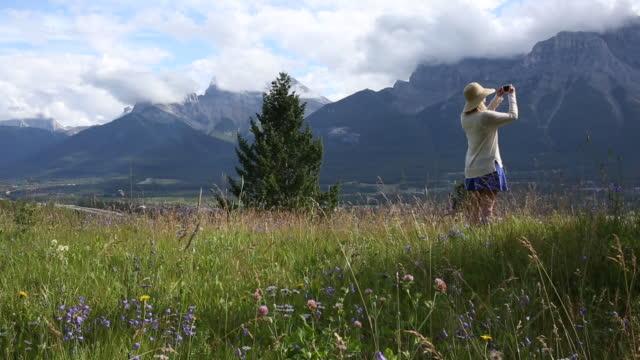 vídeos y material grabado en eventos de stock de mujer entra en el prado, se asoma a través de montañas y bosque - memorial day weekend