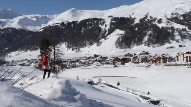 woman walks onto snow drift above village, looks out - livigno video stock e b–roll