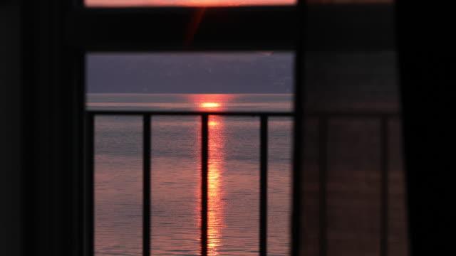 vídeos de stock e filmes b-roll de woman walks onto veranda at sunrise - lago maggiore