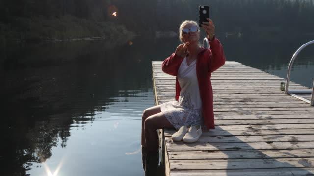 vidéos et rushes de femme se promène hors sur la jetée au lever du soleil, dans les montagnes - une seule femme d'âge mûr