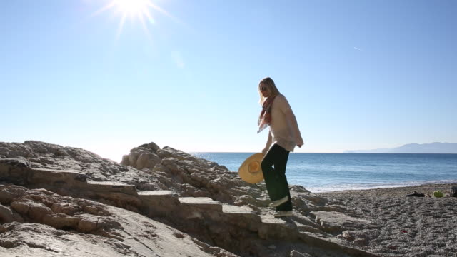Woman walks up stone staircase above beach, into sunlight  coastal feature stock videos & royalty-free footage