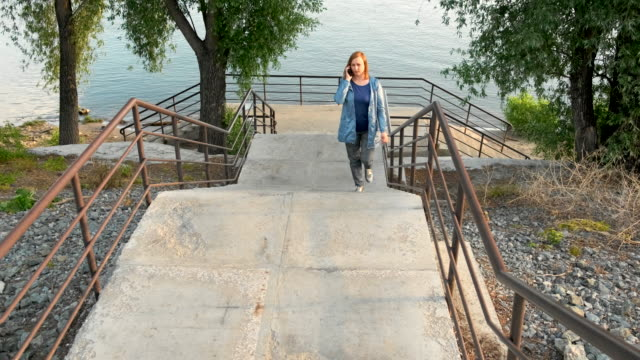 a woman walks up the stairs from the river bank - city walking background video stock e b–roll