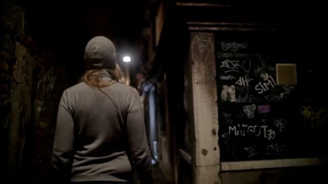 Woman wandering in dark alleyway at night
