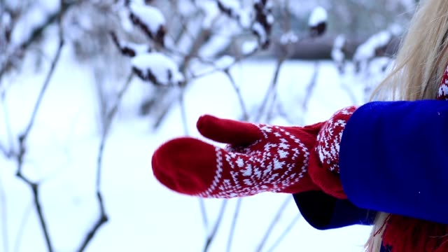 Woman warming frozen hands in mittens Closeup of young female putting on red knitted mittens to warm her frozen hands outdoors on winter day. Woman in woolen mittens rubbing her hands to warm up in wintertime over snowbound background. glove stock videos & royalty-free footage