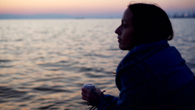 Woman warming up with hot coffee near the sea video