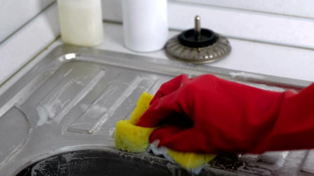 woman washes a metal sink with sponge in the kitchen in red gloves. - нержавеющая сталь стоковые видео и кадры b-roll