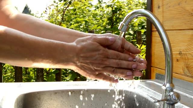 kvinnan tvättar händerna under rinnande vatten från utomhus kran i trädgården på sommaren solig dag, använda rent vatten och hygien koncept - lucia bildbanksvideor och videomaterial från bakom kulisserna