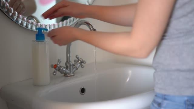 woman washes her hands with liquid soap in the bathroom. - nakładać filmów i materiałów b-roll