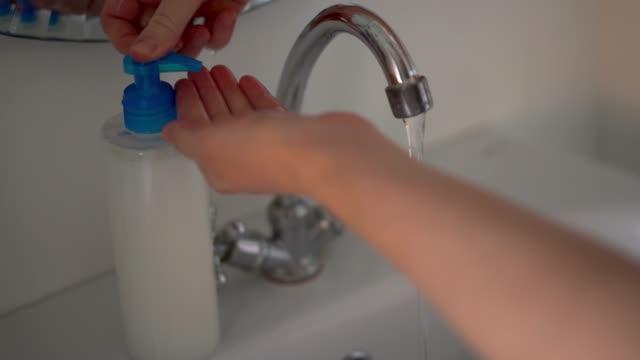 kvinnan tvättar händerna med flytande tvål i badrummet. - resistance bacteria bildbanksvideor och videomaterial från bakom kulisserna