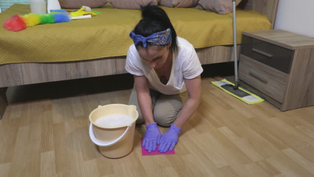 Woman washing and cleaning floor by wet rag.Cleaning,housework and housekeeping concept - vídeo