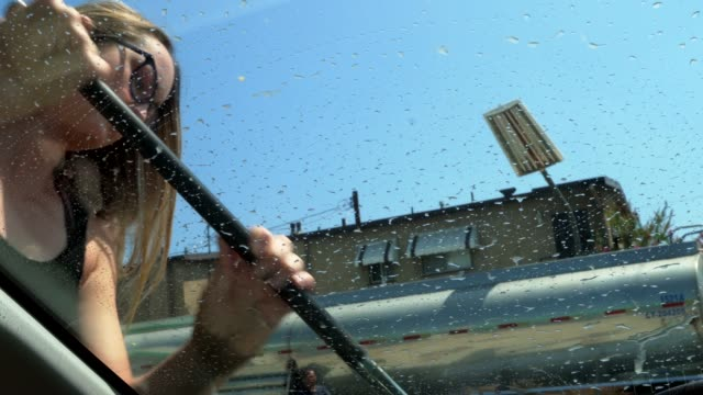 POV woman washing car windshield window with gas station squeegee