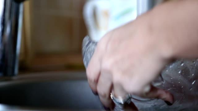 vídeos y material grabado en eventos de stock de mujer lavando los platos en la fregadero - brazo humano