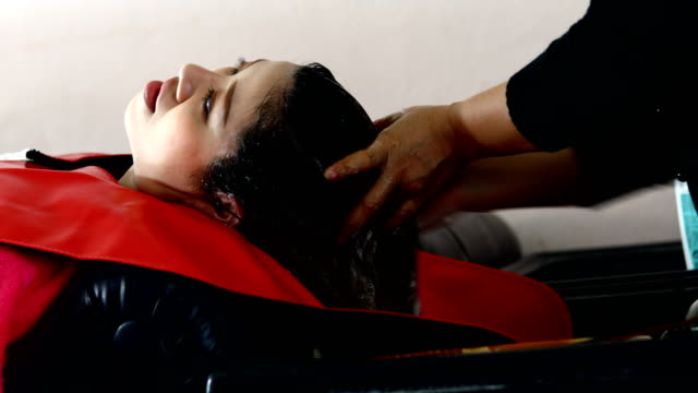 Woman washing hair in beauty salon video