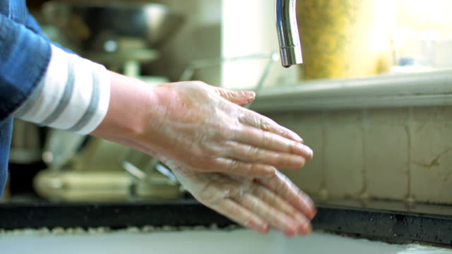 Woman washing hands with soap under running water in kitchen video
