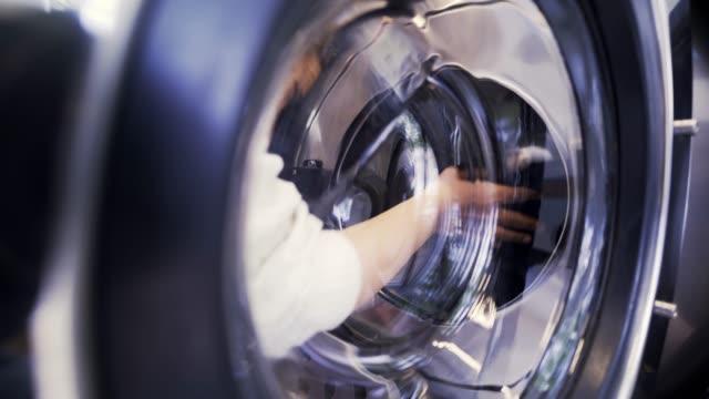 kvinna tvättning i liten tvättomat i dagsljus - dirty money bildbanksvideor och videomaterial från bakom kulisserna