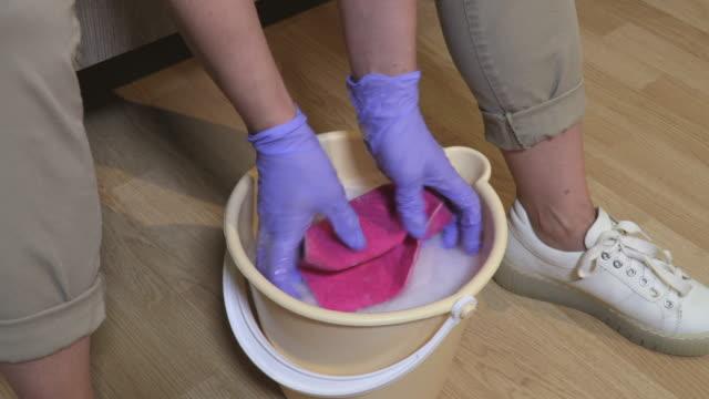 Woman washing rag in bucket on floor at home - vídeo
