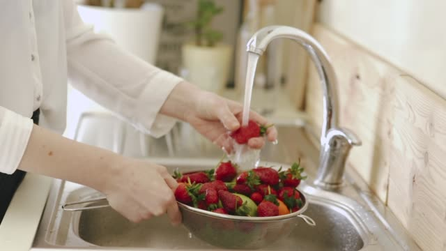 woman washing strawberries under kitchen tap - bacca video stock e b–roll