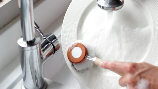 frau waschen zu hause mit eco dish brush für nachhaltigen lebensstil - essgeschirr stock-videos und b-roll-filmmaterial