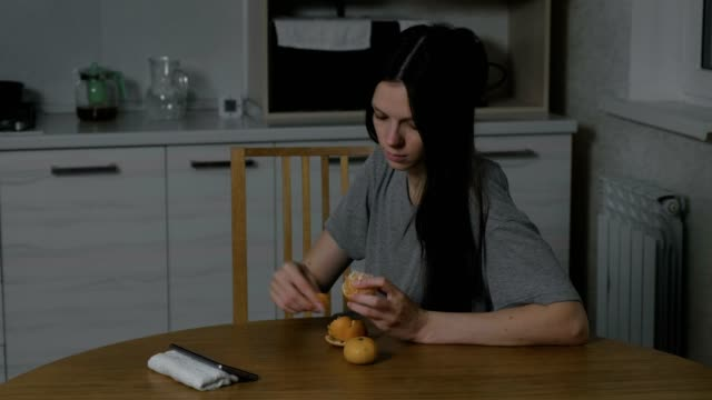 Woman watches a video at phone and eats a tangerine in the kitchen at night.