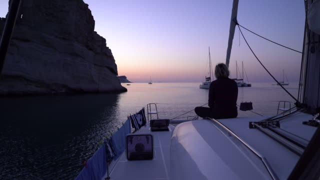 Woman watches sunset from bow of sailboat Group of middle-aged friends explore Greek island by sailboat. long hair stock videos & royalty-free footage