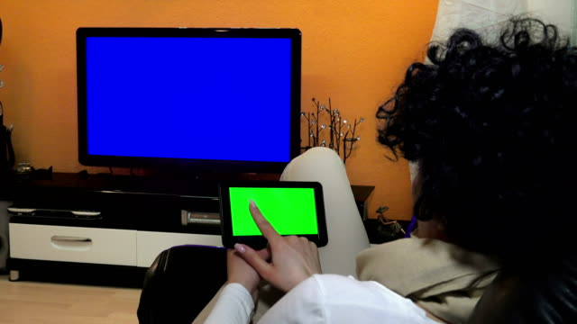 woman watches television while holding a and tapping on a tablet device. UHD stock video with luma matte video