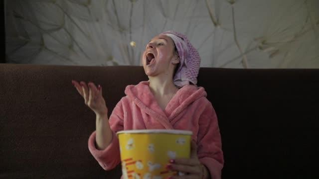 Woman watching a late night movie at TV, eating popcorn. Bathrobe, facial mask