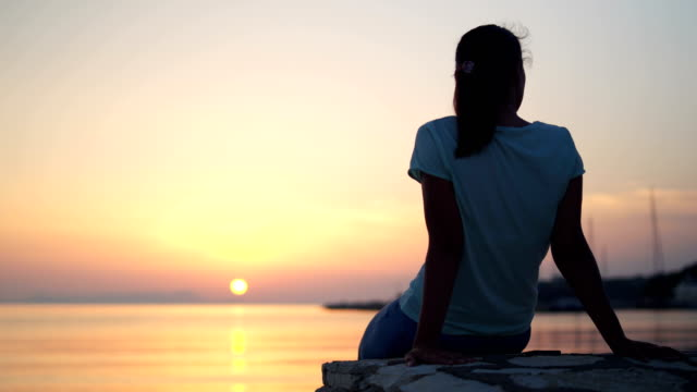 Woman watching amazing sunset over the sea