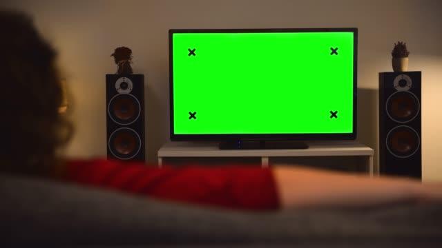 Woman watching chroma key green screen tv at home