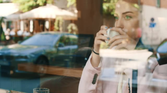 A woman watching from a cafe video