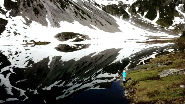 Woman watching glacier with reflections in the lake video