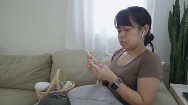 woman watching movie while crocheting at home - auricolari wireless video stock e b–roll