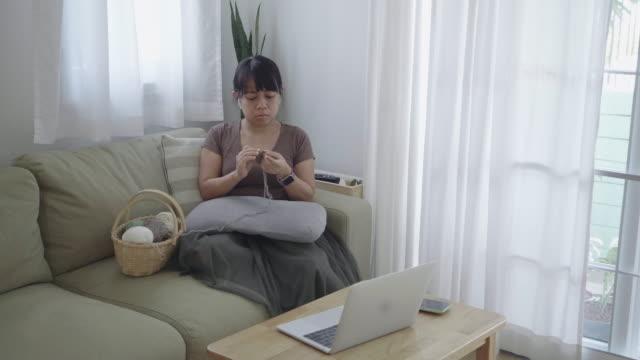 woman watching movie while crocheting - auricolari wireless video stock e b–roll