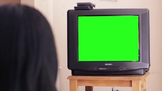 frau beobachten alten fernseher mit grünem bildschirm. - tv stock-videos und b-roll-filmmaterial