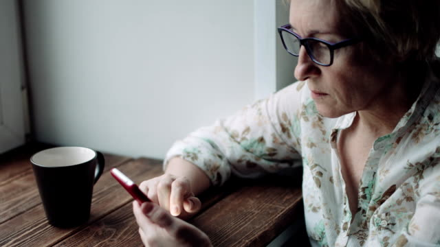 Woman watching something on the smartphone screen Side view shot of adult woman in glasses watching something on the smartphone screen 50 54 years stock videos & royalty-free footage