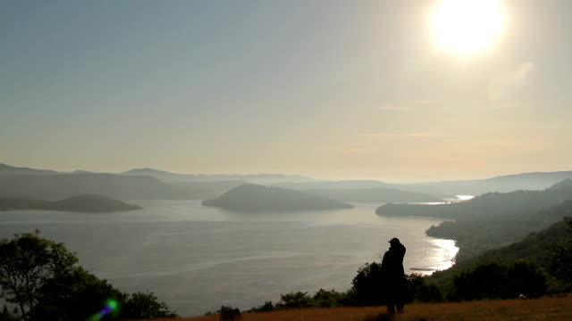 Woman watching the sunset over a giant lake with islands video
