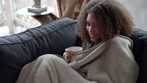 kobieta oglądająca telewizję zakrywając się kocem i pijąc kawę w zimny zimowy poranek - relaks filmów i materiałów b-roll