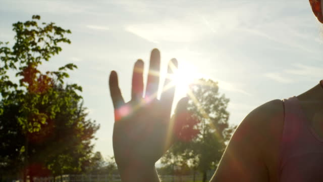 SLOW MOTION CLOSE UP: Woman waving goodbye SLOW MOTION CLOSE UP: Woman waving goodbye, sun shining through the fingers goodbye single word stock videos & royalty-free footage