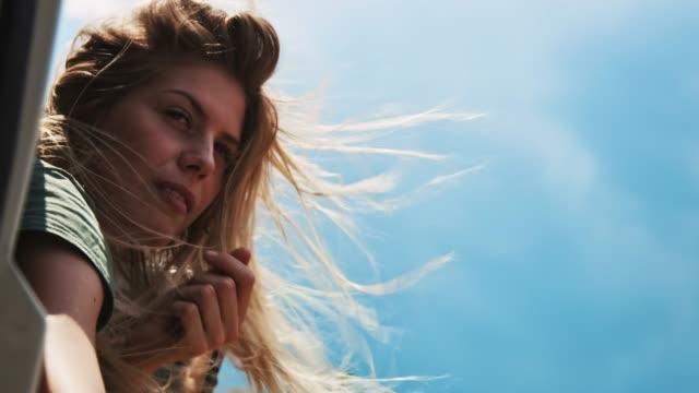 stockvideo's en b-roll-footage met vrouw zwaaien hand tijdens road trip - hair woman