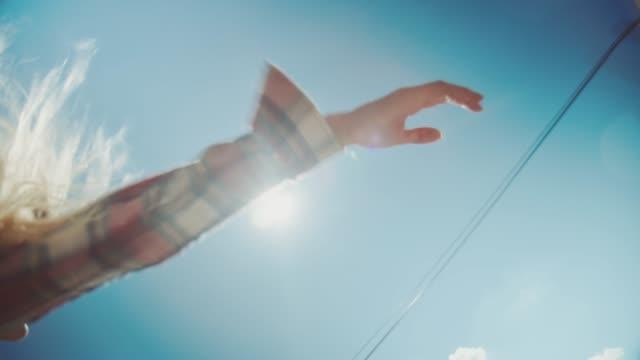 Woman waving hands through van window on sunny day