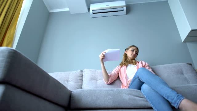 kvinna vifta papper sitter på soffan, lidande värme, felaktig luftkonditionering - kvinna ventilationssystem bildbanksvideor och videomaterial från bakom kulisserna