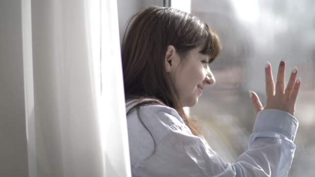 woman waving to the window to someone, welcomes video