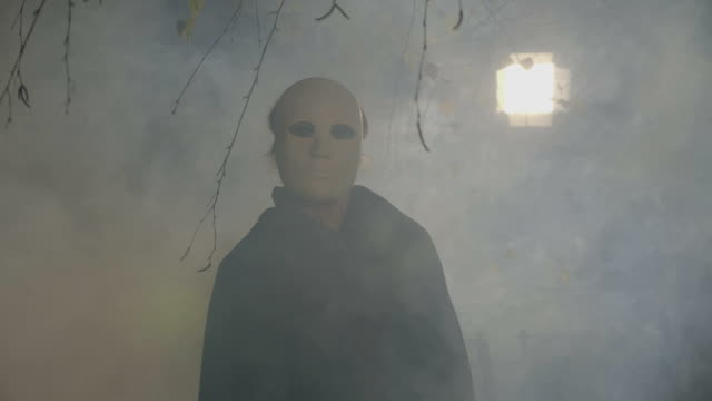 Woman wearing a black cape and a white mask hiding and revealing her face to the camera on halloween holiday video