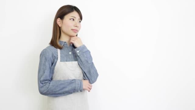 エプロンを着た女性 - 悩む点の映像素材/bロール