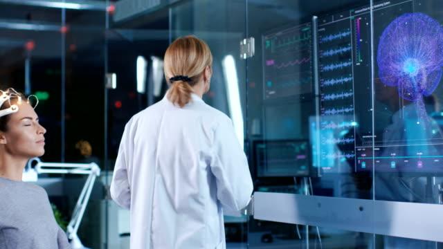 frau trägt brainwave scannen kopfhörer sitzt auf einem stuhl während wissenschaftler betreut. in den modernen gehirn studie labor monitore zeigen eeg lesung und gehirn modell. - wissenschaftlerin stock-videos und b-roll-filmmaterial