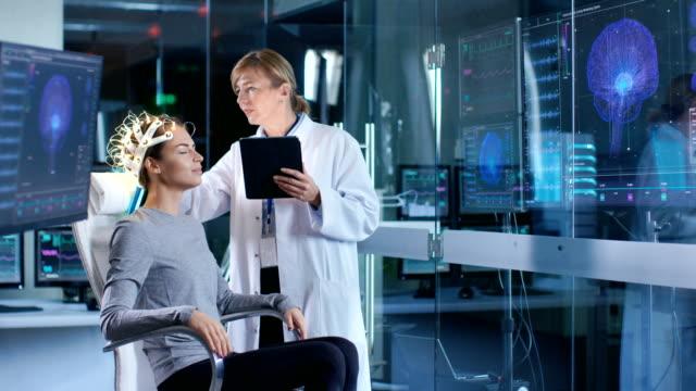 woman wearing brainwave scanning kopfhörer sitzt auf einem stuhl während wissenschaftler passt das gerät tablet-computer verwendet. in den modernen gehirn studie labor monitore zeigen eeg lesung und gehirn modell. - wissenschaftlerin stock-videos und b-roll-filmmaterial