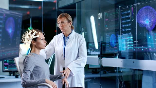frau trägt brainwave scannen kopfhörer sitzt auf einem stuhl während wissenschaftler passt das gerät schaut displays. in den modernen gehirn studie labor monitore zeigen eeg lesung und gehirn modell. - wissenschaftlerin stock-videos und b-roll-filmmaterial
